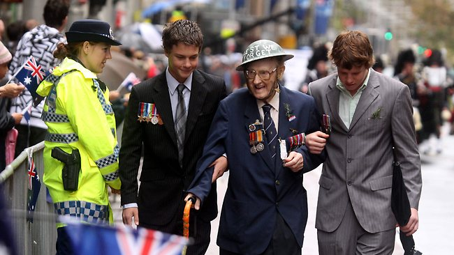 A Digger is flanked by two young men displaying the medals of a relatives in the Anzac Day Parade, 2011.